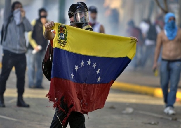 An anti-government student holds a tore Venezuelan flag during a protest in Caracas on February 15, 2014. Supporters and opponents of Venezuela's leftist government staged dueling rallies in Caracas and other cities in the latest public displays of discontent at soaring inflation and basic goods shortages. AFP PHOTO/ JUAN BARRETO