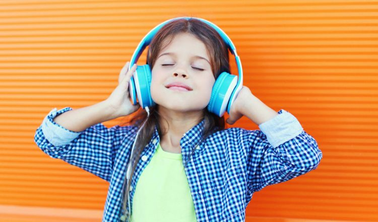 Happy smiling child enjoys listens to music in headphones over colorful orange background